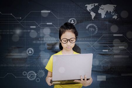 Female elementary school student using a laptop computer while standing with virtual screen background