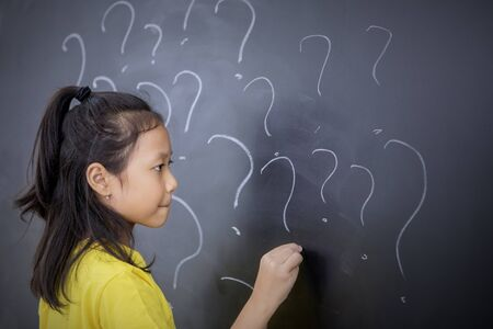 Female elementary school student drawing question marks on the blackboard. Shot in the classroom