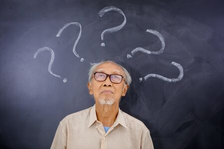 Picture of elderly man looking at question marks over his head in a blackboard