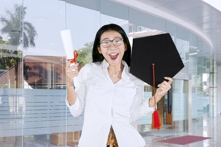 Picture of cheerful woman celebrating his graduation by lifting a graduation cap and diploma