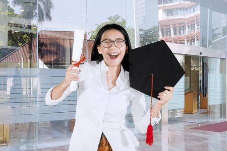 Picture of happy woman celebrating his graduation by lifting a graduation cap and diploma