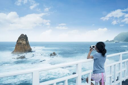 Rear view of little girl using a camera to taking a photo of Papuma beach in Jember at East Java, Indonesia Stok Fotoğraf