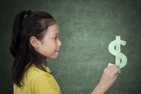 Picture of Female elementary school student drawing dollar sign on the chalkboard. Shot in the classroom Stok Fotoğraf