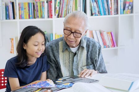Old man teaching his granddaughter to read a book while sitting together in the library