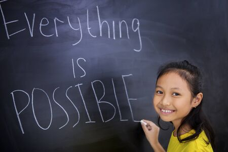 Happy schoolgirl writing text of everything is possible on a blackboard while standing in the classroom