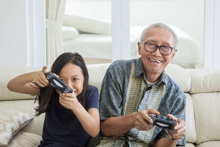 Cheerful little girl playing video games with her grandfather while sitting on the sofa. Shot at home Stok Fotoğraf