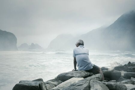 Rear view of old man sitting on the stone while enjoying foggy Papuma beach view at morning time
