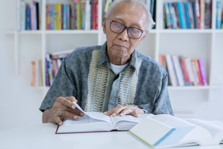 Picture of senior man wearing glasses while reading a textbook in the library with bookcase background