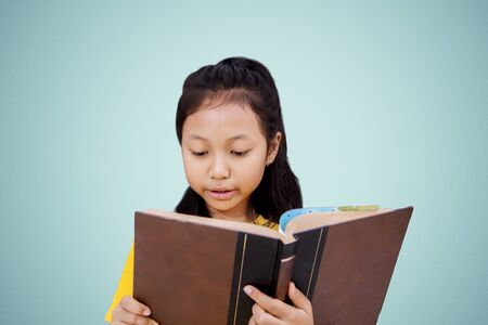 Female elementary school student reading a book while standing in the studio