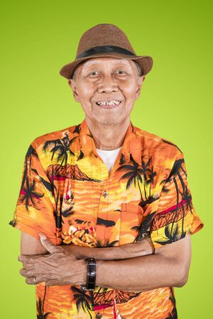 Close up of confident senior man wearing summer clothes while standing in the studio with green screen background
