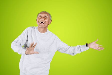 Picture of elderly man looks happy while dancing in the studio with green screen background Stok Fotoğraf