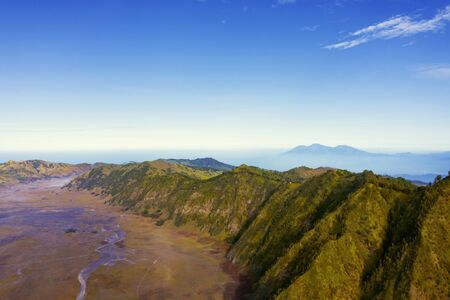 Beautiful aerial view of Kingkong hill under blue sky at misty morning in East Java, Indonesia
