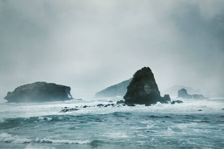 Beautiful scenery of misty morning at Papuma beach with big corals in Jember at East Java, Indonesia