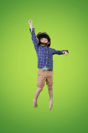 Portrait of little boy wearing a flight helmet while flying in the studio with green screen