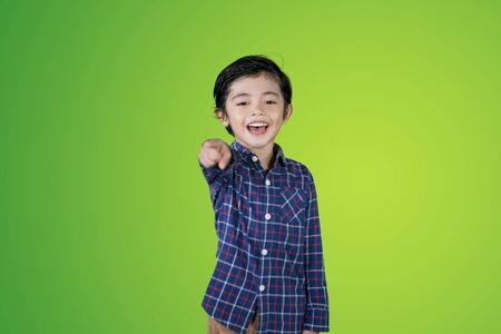 Picture of little boy looks happy while pointing and mocking somebody in the studio with green screen