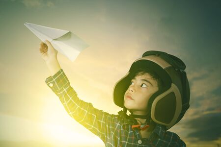 Picture of a cute male pilot wearing helmet while playing a paper plane in sunrise background
