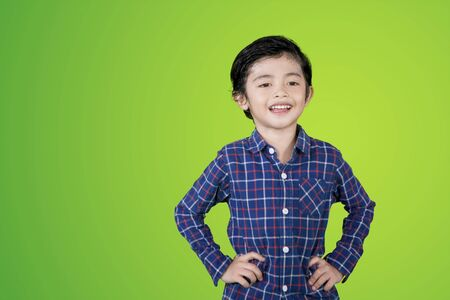 Picture of cute little boy smiling at the camera while standing in the studio with green screen background