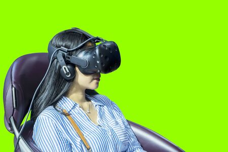 Picture of young woman using a VR glasses to playing a game simulator and sitting on a seat Stok Fotoğraf
