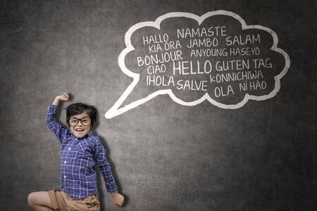 Picture of cute little boy looks happy while learning multilingual and jumping with a cloud bubble