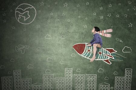 Picture of cute little boy riding a drawn rocket while flying over buildings with chalkboard background