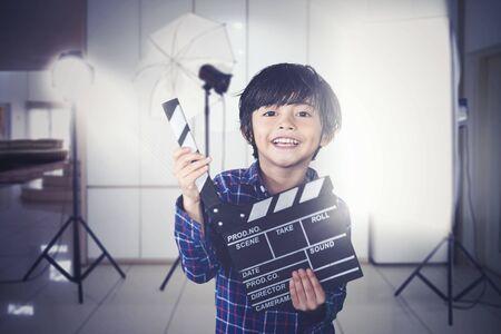 Foto van een kleine jongen ziet er gelukkig uit terwijl hij de filmklapper vasthoudt tijdens de filmproductie Stockfoto