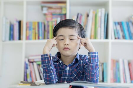 Image of a little boy thinking with eyes closed while learning in the library with bookshelf background Stok Fotoğraf
