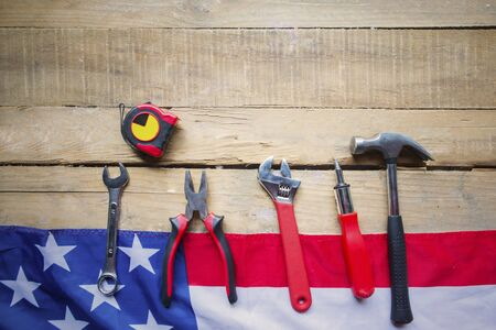 Top view of handy tools with American flag on the wooden table