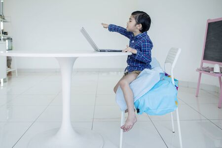 Picture of Asian little boy looks angry while watching a movie on a laptop computer and sitting on a chair