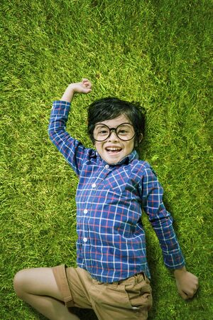 Top view of a cheerful little boy looking at the camera while lying down on the grass Stok Fotoğraf