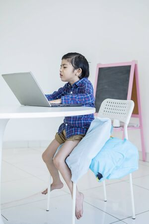Picture of little boy looks angry while using a laptop computer and sitting on a chair