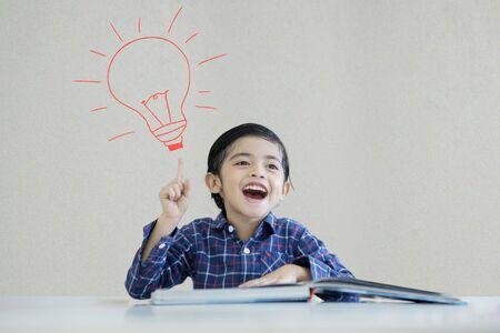 Foto van een kleine jongen die een boek leest terwijl hij een idee denkt en onder een getekende gloeilamp zit
