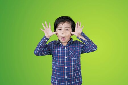 Little boy showing a mocking with sticking out tongues at the camera with green screen background