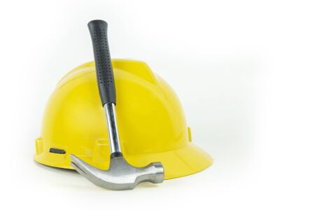 Labor Day concept. Image of hammer with yellow helmet, isolated on white background