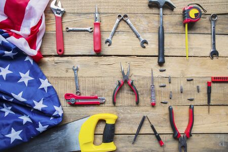 Top view of an American flag and handy tools shaping a text of Happy Labor Day on the wooden table