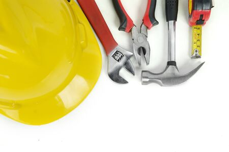 Top view of handy tools with yellow helmet on the table, isolated on white background