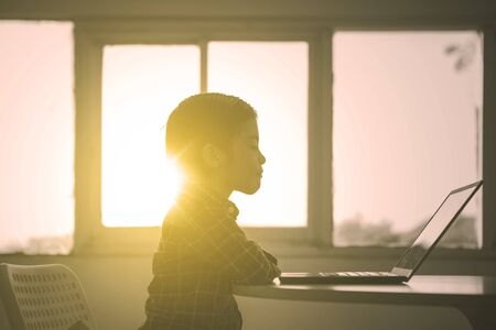 Silhouette of little boy watching a movie on a laptop computer at sunset time