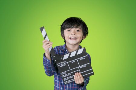 Picture of happy little boy holding a clapperboard while standing in the studio with green screen background
