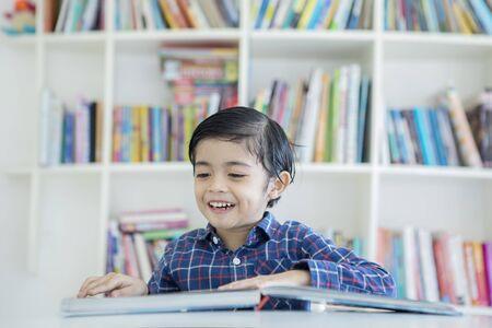 Foto van een Aziatische kleine jongen die een boek leest terwijl hij studeert in de bibliotheek met een boekenkastachtergrond Stockfoto