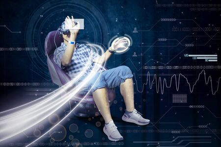 Picture of young man wearing a VR glasses while touching virtual button and sitting on chair