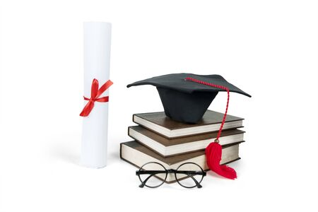 Top view of graduation hats and diploma with a pile of books on the table, isolated on white background