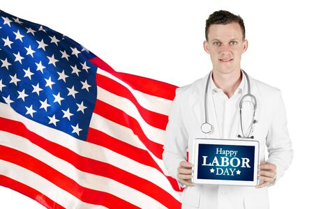 Caucasian male doctor showing Happy Labor Day text on the tablet while standing with American flag in the studio Stok Fotoğraf