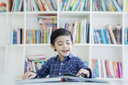 Picture of cute little boy reading a book while studying in the library with bookcase background Stok Fotoğraf
