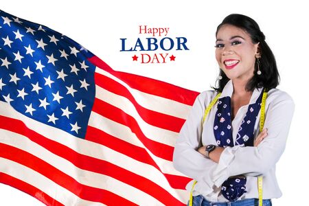 Female fashion designer smiling at the camera while standing with American flag and Happy Labor Day text in the studio