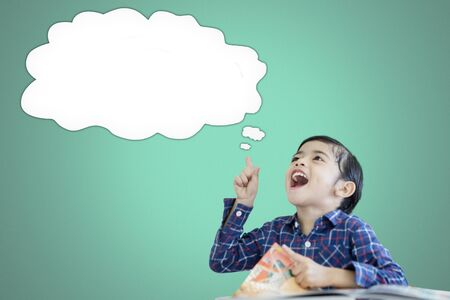 Picture of a little boy thinking an idea while pointing an empty cloud bubble in the studio