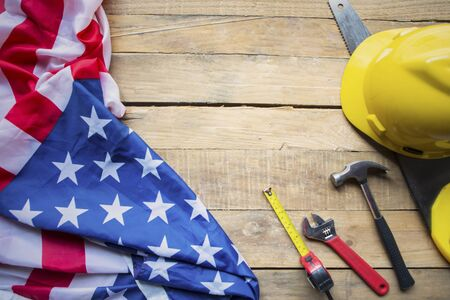 Top view of American flag with construction tools on the wooden table. Labor Day concept