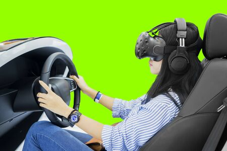 Young woman playing racing video game with a VR headset while driving in a simulator car with green screen background