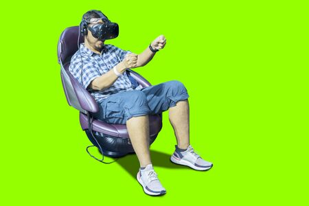 Picture of young man using a VR glasses to playing a racing game with green screen background Stok Fotoğraf