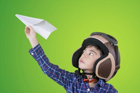 Little boy wearing flight helmet while playing a paper plane in the studio with green screen background