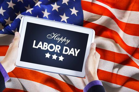 Close up of businessman hands holding Happy Labor Day text on a digital tablet with American flag background