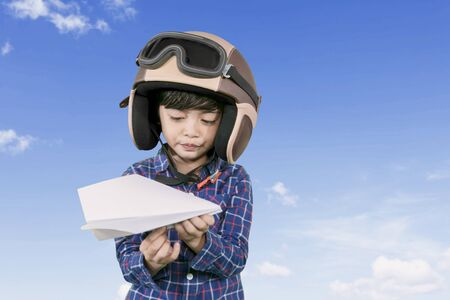 Picture of little male pilot wearing helmet while holding a paper plane with blue sky background Stok Fotoğraf